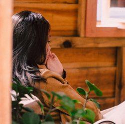 Kvinde sidder i træhus